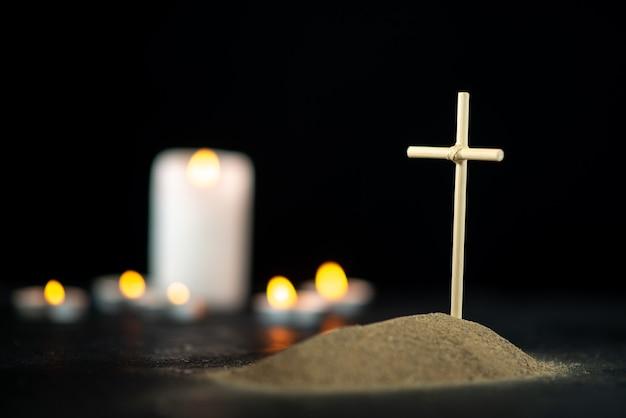 Vista frontal da pequena sepultura com velas no preto