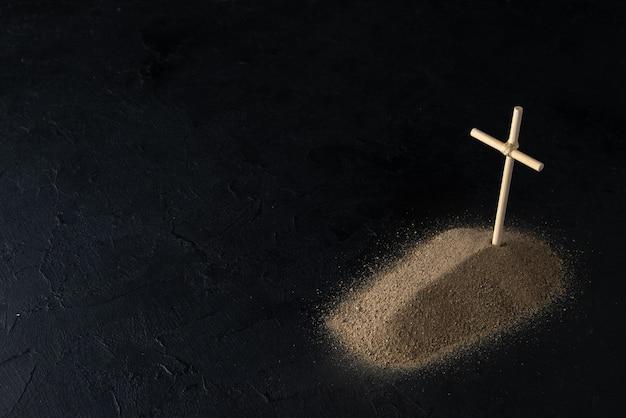 Vista frontal da pequena sepultura na areia com uma cruz de pau no preto
