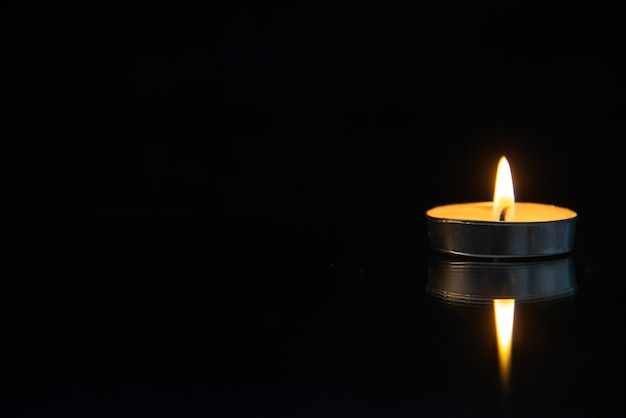 Vista frontal da pequena vela acesa no preto