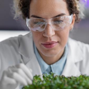 Vista frontal da pesquisadora no laboratório com óculos de segurança e planta