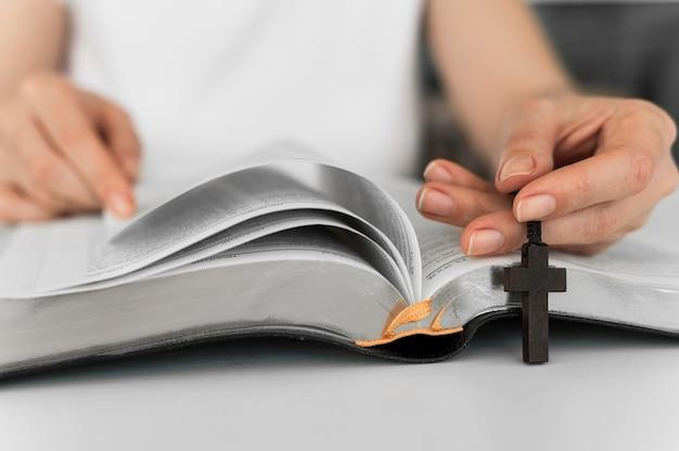 Vista frontal da pessoa com leitura cruzada do livro sagrado