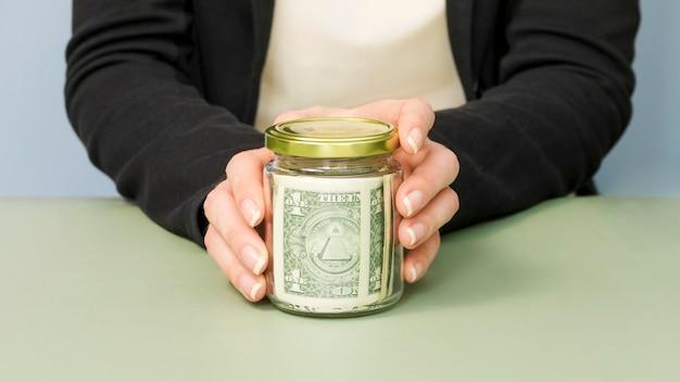 Vista frontal da pessoa com um pote de dinheiro
