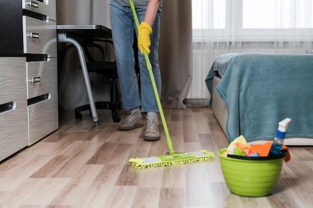 Vista frontal da pessoa limpando chão no quarto