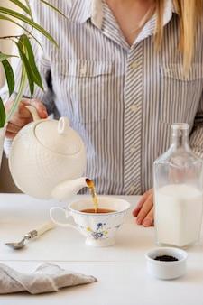 Vista frontal da pessoa preparando chá de leite