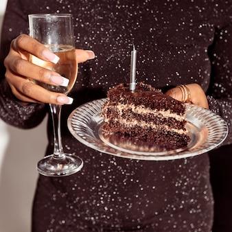 Vista frontal da pessoa segurando bolo e champanhe