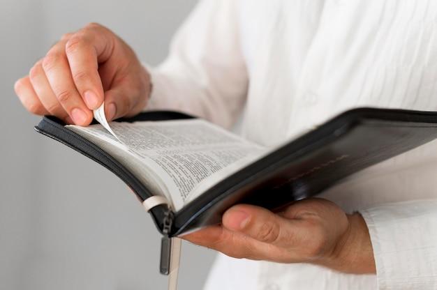 Vista frontal da pessoa segurando o livro sagrado