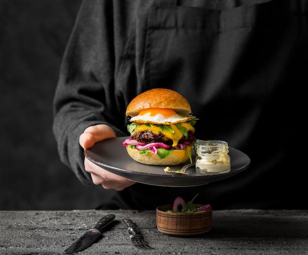Vista frontal da pessoa segurando o prato com hambúrguer