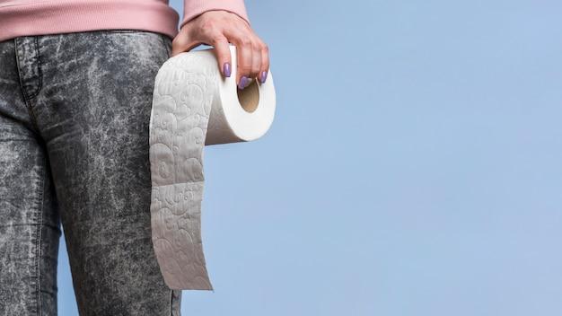 Vista frontal da pessoa segurando o rolo de papel higiênico com espaço de cópia