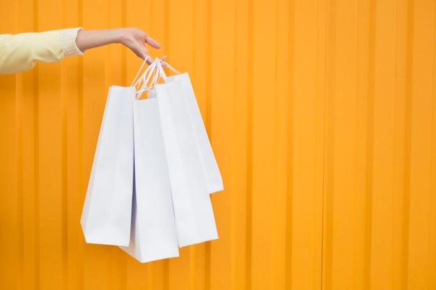 Vista frontal da pessoa segurando sacolas de compras brancas copiar o espaço