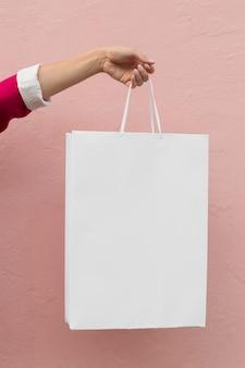 Vista frontal da pessoa segurando sacolas de compras brancas