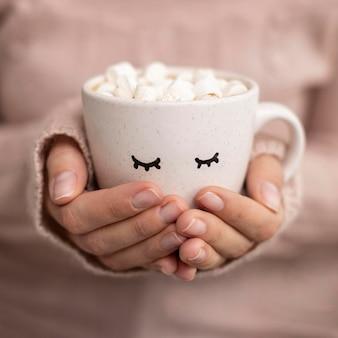 Vista frontal da pessoa segurando uma xícara de chocolate quente com marshmallows