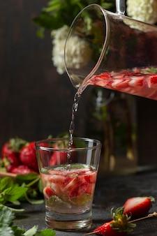 Vista frontal da pessoa servindo água com infusão de morango