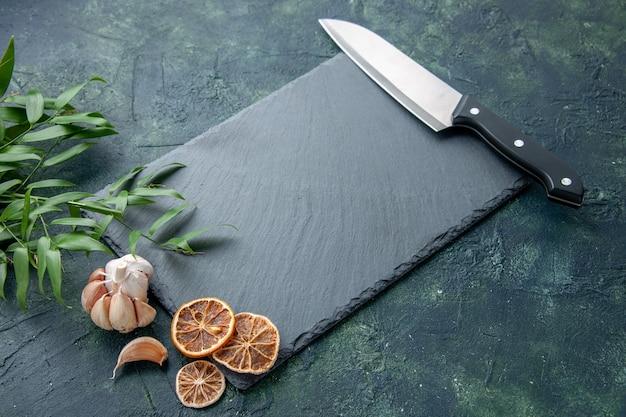 Vista frontal da placa cinza com grande faca na foto colorida de fundo azul escuro mesa de cozinha de frutos do mar em azul acentuado