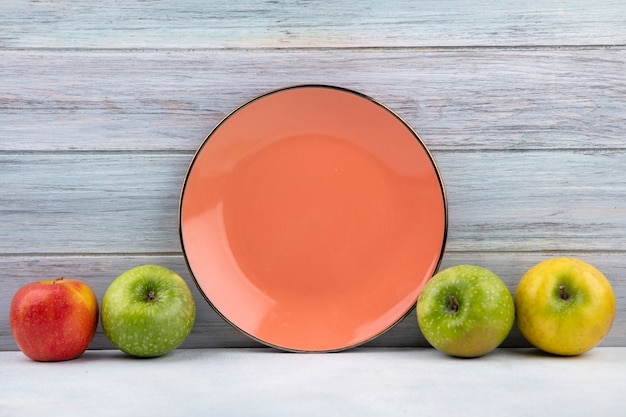 Vista frontal da placa laranja com maçãs coloridas e frescas na superfície de madeira