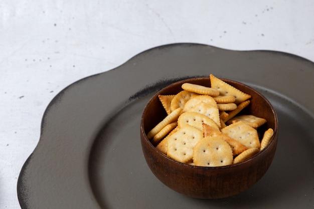 Vista frontal da placa marrom com biscoitos e batatas fritas na superfície da luz
