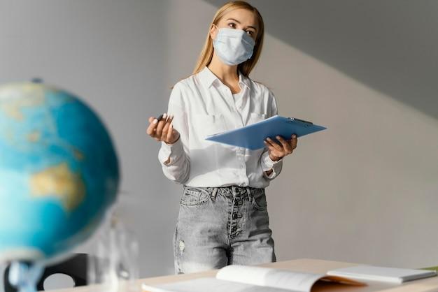 Vista frontal da professora em sala de aula com a prancheta