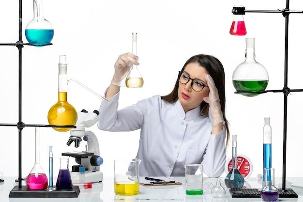 Vista frontal da química feminina em traje médico branco segurando a solução sobre o vírus de laboratório pandêmico de covid-ciência de fundo branco
