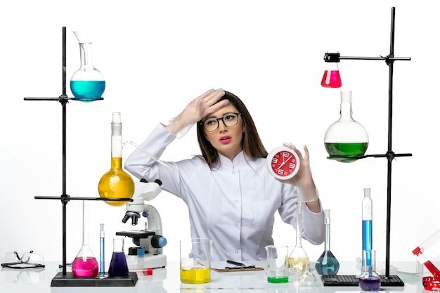 Vista frontal da química feminina em traje médico branco segurando relógios vermelhos no laboratório de covidemia de vírus de ciência de fundo branco