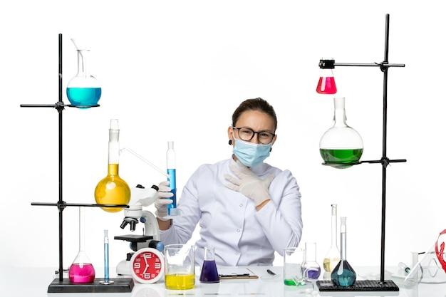 Vista frontal da química feminina em traje médico com máscara segurando o frasco com solução azul no piso branco respingo vírus laboratório de química covid
