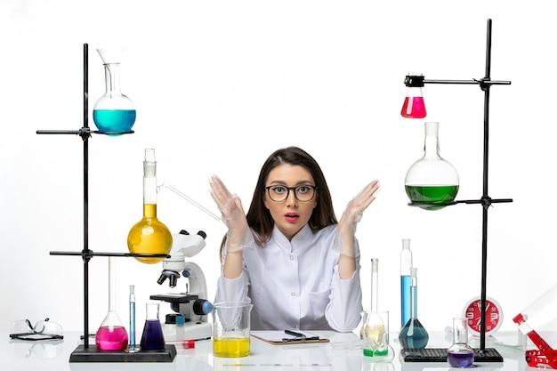 Vista frontal da química feminina em traje médico, sentada ao redor da mesa com soluções na mesa branca, vírus de laboratório, ciência da pandemia
