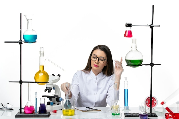 Vista frontal da química feminina em um terno médico branco segurando um frasco com uma solução azul na luz de fundo branco laboratório ciência vírus covid pandemia