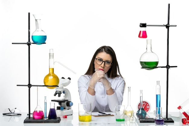 Vista frontal da química feminina em um terno médico branco sentada com diferentes soluções no laboratório de vírus pandêmico de ciência de mesa branca