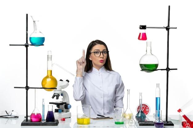 Vista frontal da química feminina em um terno médico branco sentada com soluções no laboratório covid de vírus pandêmico de ciência de fundo branco