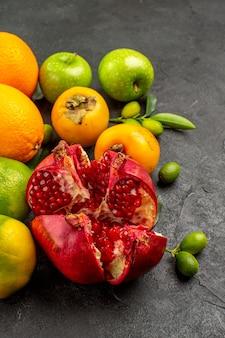 Vista frontal da romã fresca com maçãs e outras frutas na superfície cinza de cor de frutas maduras