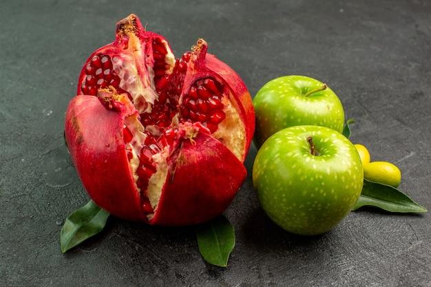 Vista frontal da romã fresca com maçãs verdes na superfície escura, cor de frutas maduras