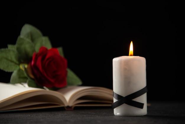 Vista frontal da rosa vermelha com livro e vela no preto
