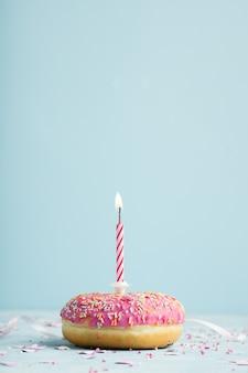 Vista frontal da rosquinha de aniversário com vela acesa e cópia espaço