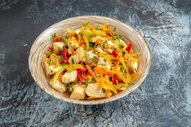 Vista frontal da salada de frango com legumes na superfície clara