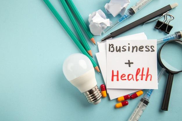 Vista frontal da saúde do negócio com comprimidos, lápis e injeções sobre fundo azul