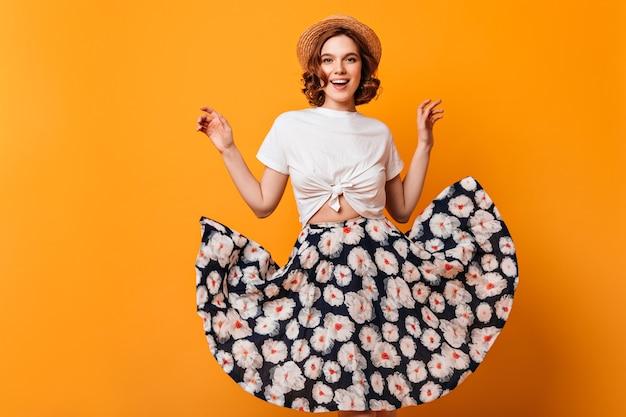 Vista frontal da senhora inspirada no chapéu de palha. foto de estúdio de linda garota sorridente com saia na moda, posando em fundo amarelo.