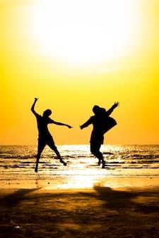 Vista frontal da silhueta jovem e jovem pulando sobre a praia do mar com fundo por do sol.