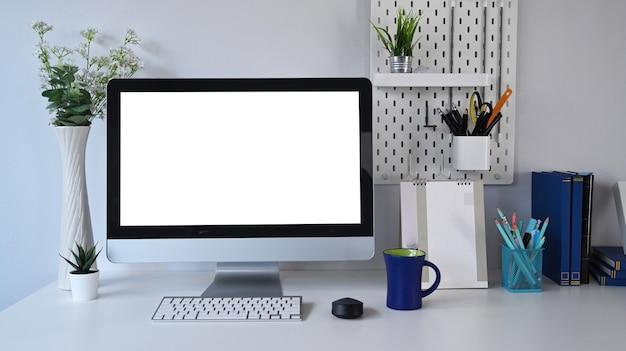 Vista frontal da simulação de computador com tela em branco e material de escritório na mesa branca no elegante local de trabalho.