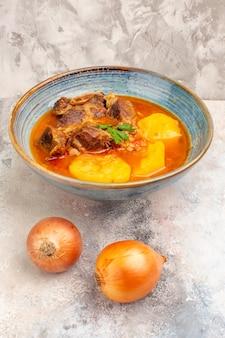 Vista frontal da sopa bozbash em uma tigela e cebola nua