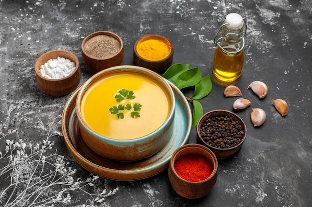 Vista frontal da sopa de abóbora com temperos em uma mesa escura. jantar suave de ação de graças