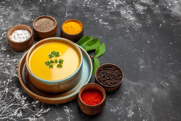 Vista frontal da sopa de abóbora com temperos na mesa escura