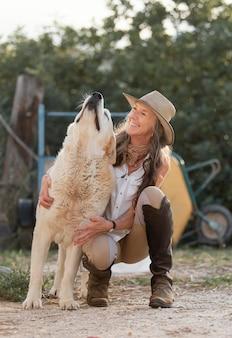 Vista frontal da sorridente agricultora com seu cachorro de fazenda