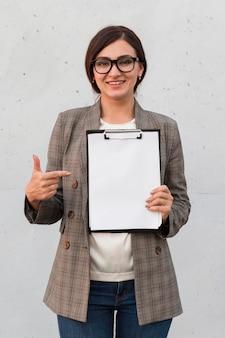 Vista frontal da sorridente empresária apontando para o bloco de notas