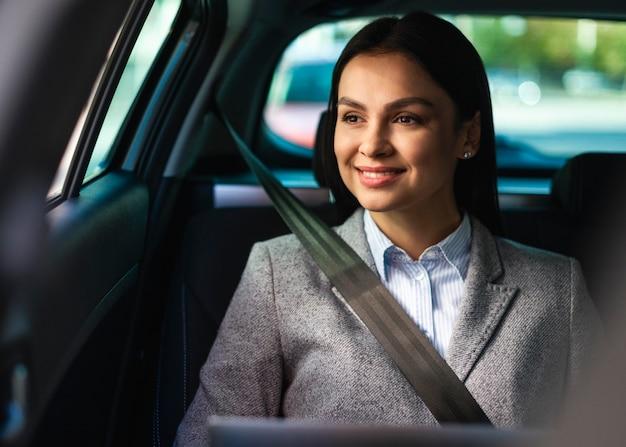 Vista frontal da sorridente empresária no carro