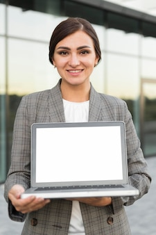 Vista frontal da sorridente empresária segurando um laptop