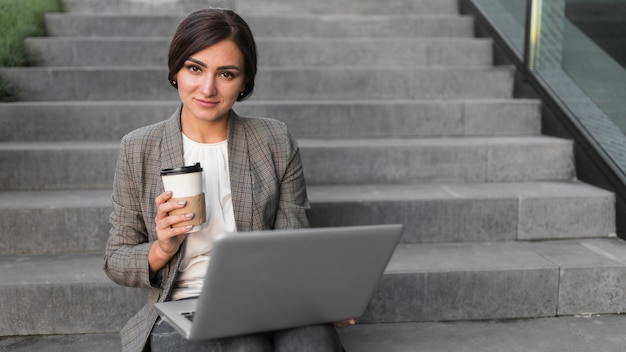 Vista frontal da sorridente empresária trabalhando em um laptop nas escadas