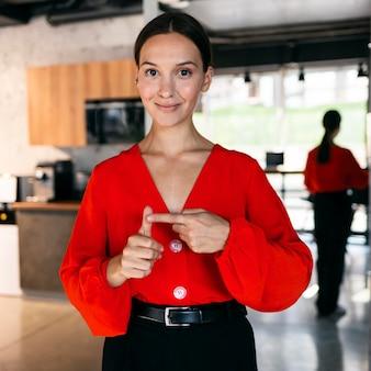 Vista frontal da sorridente empresária usando linguagem de sinais