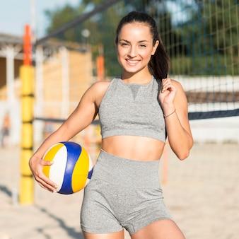 Vista frontal da sorridente jogadora de vôlei na praia, posando com a bola