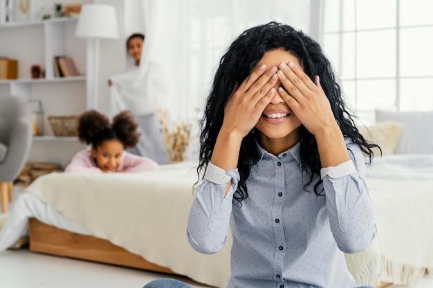 Vista frontal da sorridente mãe brincando de esconde-esconde com seus filhos