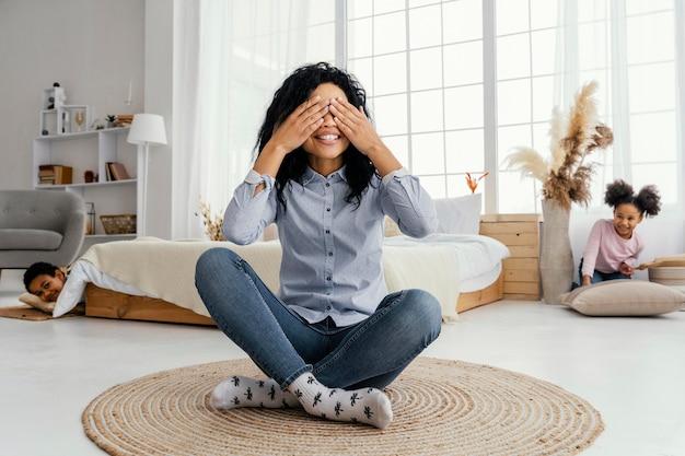 Vista frontal da sorridente mãe brincando de esconde-esconde em casa com seus filhos