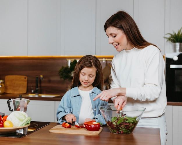 Vista frontal da sorridente mãe e filha preparando comida na cozinha