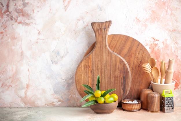 Vista frontal da tábua de cortar colheres de madeira ralador kumquats no pote na superfície colorida